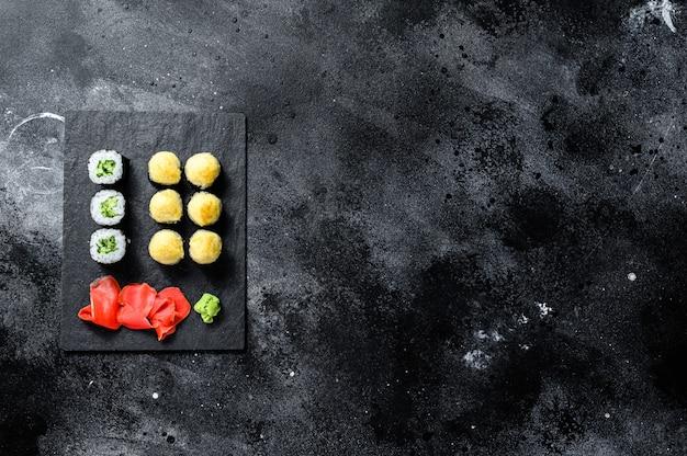 Roladki sushi z ogórkiem, łososiem i krewetkami na kamiennej tacy.