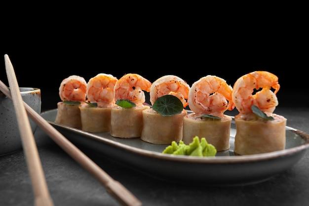 Roladki sushi z omletem, krewetkami i paluszkami krabowymi na ciemnym tle