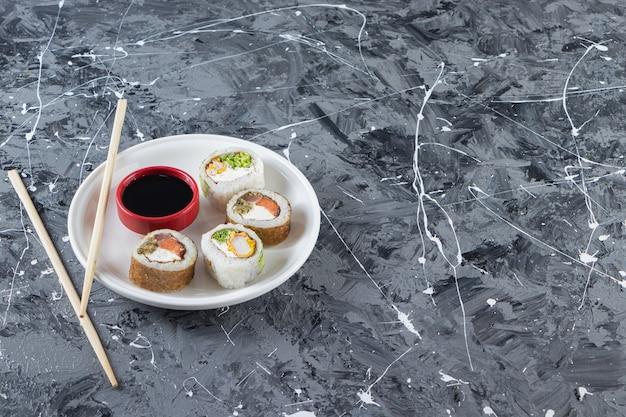 Roladki sushi z sosem sojowym ułożone na białym talerzu pałeczkami.