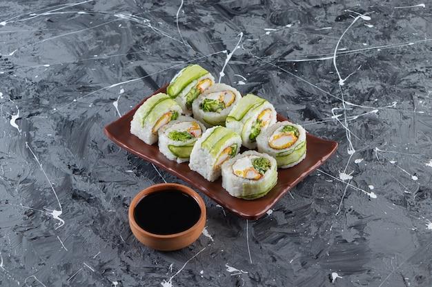 Roladki sushi z sosem sojowym ułożone na brązowym talerzu.