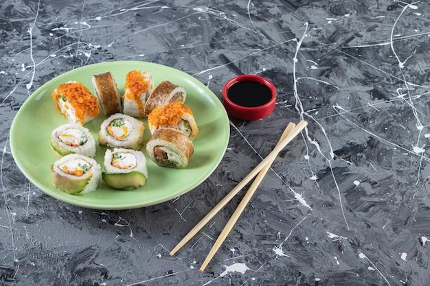 Roladki sushi z sosem sojowym ułożone na zielonym talerzu pałeczkami.