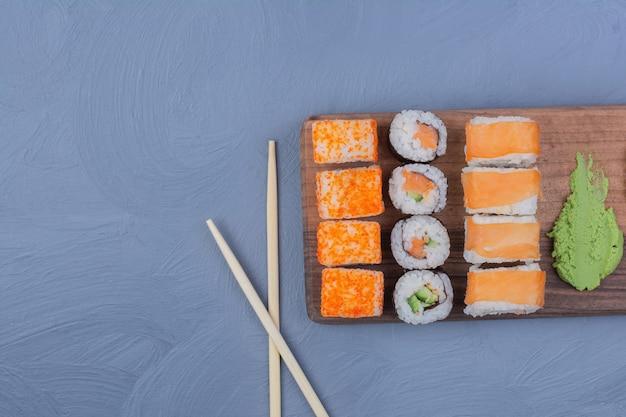 Roladki sushi z sosem wasabi na drewnianym talerzu