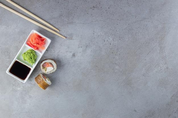 Roladki sushi z tuńczykiem, wasabi, imbirem i sosem sojowym na kamiennym tle.