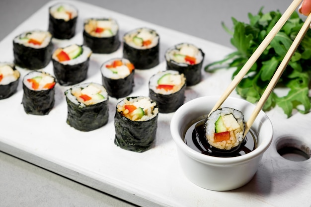 Roladki sushi z warzywami quinoa i sosem sojowym na białym talerzu