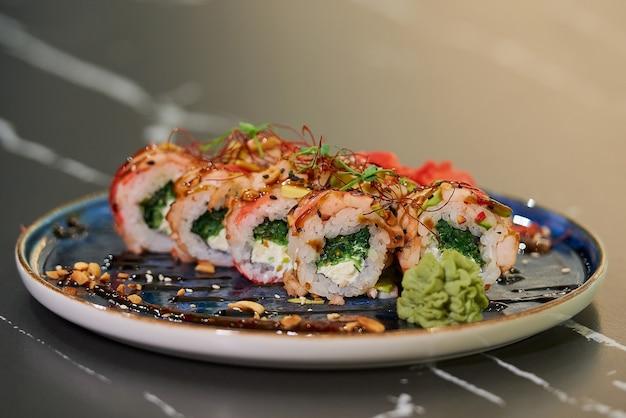 Roladki sushi z wodorostami chuka wakame, serkiem philadelphia i krewetkami na niebieskim talerzu ceramicznym z sosem, orzeszkami ziemnymi, imbirem i wasabi. stół z czarnego kamienia.