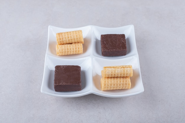 Roladki waflowe i wafel w czekoladzie w naczyniu na marmurowym stole.