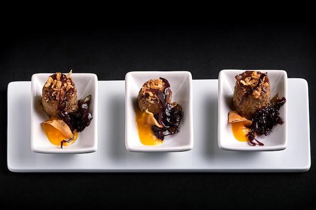 Roladki wołowe canapes z sosem dyniowym, na białych talerzach