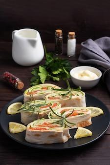 Roladki z cienkiej pita i czerwonego solonego łososia z liśćmi sałaty na czarnym talerzu ceramicznym, ciemne podłoże drewniane. skopiuj miejsce.