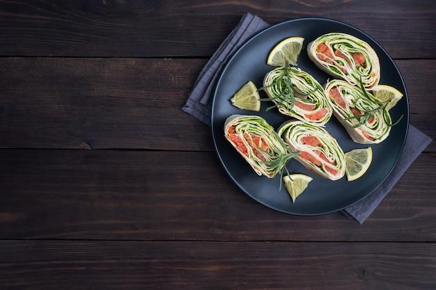 Roladki z cienkiej pita i czerwonego solonego łososia z liśćmi sałaty na czarnym talerzu ceramicznym, stół z ciemnego drewna. skopiuj miejsce.