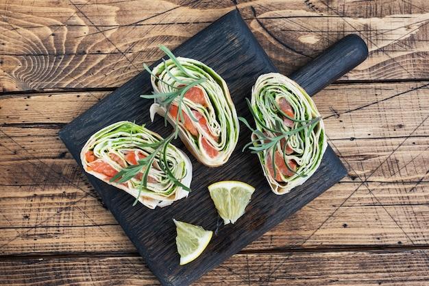 Roladki z cienkiej pita i czerwonego solonego łososia z liśćmi sałaty na drewnianej desce do krojenia. skopiuj miejsce.