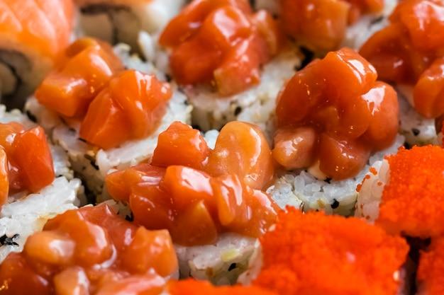 Roladki z czerwonym mięsem rybnym w sosie pomidorowym z plastrami świeżych pomidorów. japońskie jedzenie, zbliżenie