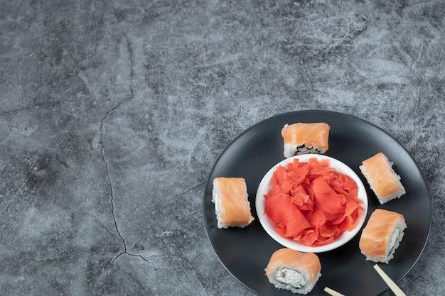 Roladki z łososia na czarnym talerzu z czerwonym marynowanym imbirem.