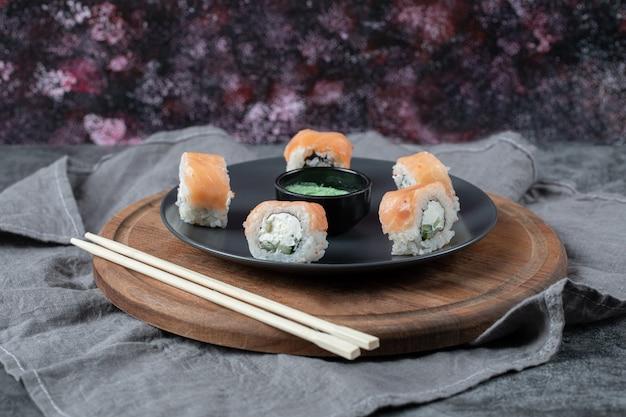 Roladki z łososia na czarnym talerzu z sosem wasabi.