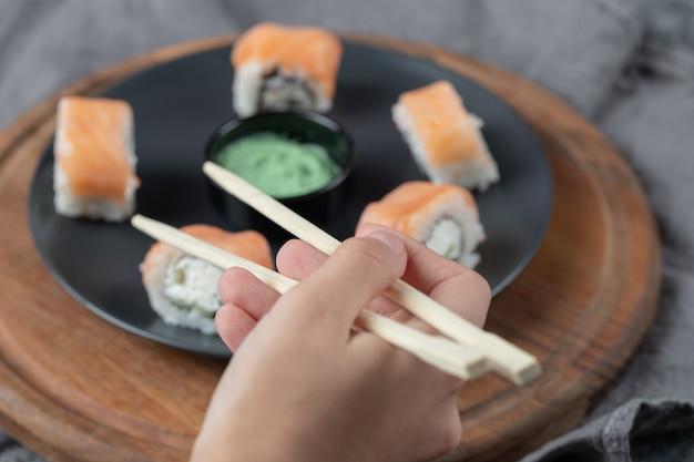 Roladki z łososia z twarogiem na czarnym talerzu z sosem wasabi.