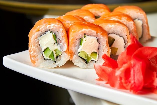 Roladki z łososiem i ogórkiem, serem i wasabi na białym talerzu