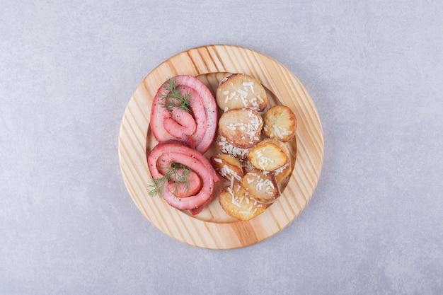 Roladki z szynką i smażone ziemniaki na drewnianym talerzu.