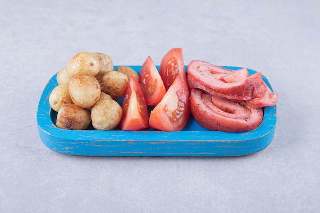 Roladki z szynką, pomidory i smażone ziemniaki na niebieskim talerzu.