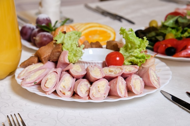 Roladki z szynki i miękkiego sera oraz szaszłyki na białym talerzu z sałatą, sosem i pomidorami.