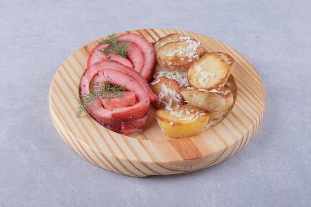 Roladki z szynki i smażone ziemniaki na kawałku drewna.