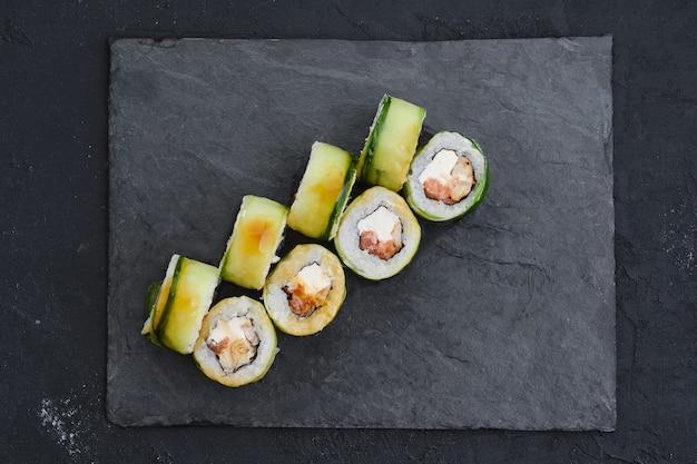 Roladki z węgorzem, ogórkiem i tuńczykiem na talerzu łupkowym