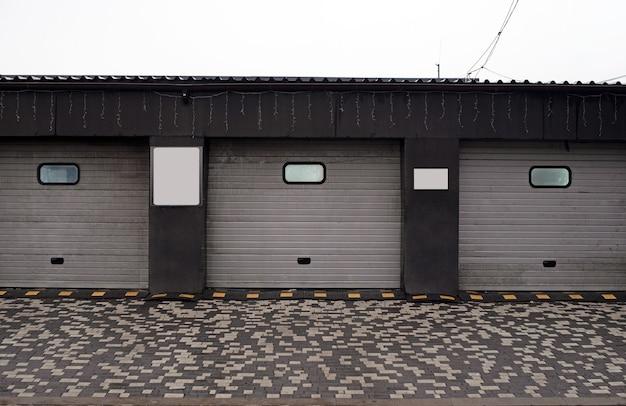 Rolety garażowe. zamknięta myjnia samochodowa, automatyczna elektryczna brama zwijana lub push-up. drzwi żaluzjowe lub rolowane i ściana z cegieł na zewnątrz.