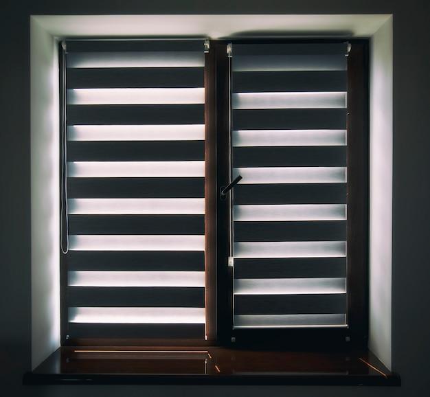 Rolety na plastikowym brązowym oknie w salonie