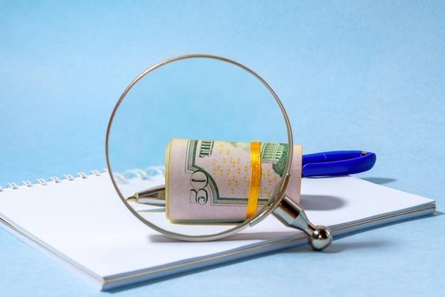 Rolka banknotów dolarowych przez szkło powiększające
