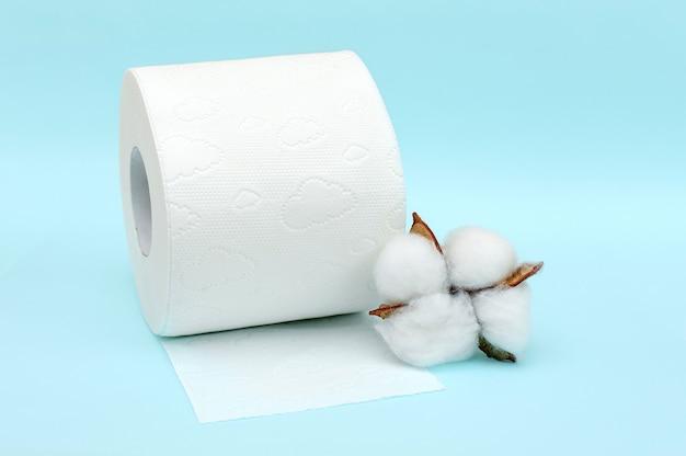 Rolka białego papieru toaletowego i bawełny kwiat na niebieskim tle