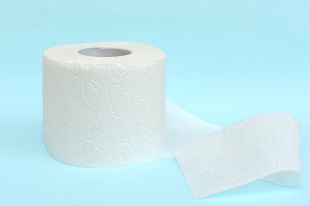 Rolka białego papieru toaletowego na niebieskim tle