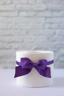 Rolka białego papieru toaletowego przewiązanego fioletową wstążką z kokardką, orientacja pionowa. papier toaletowy z liliową kokardą