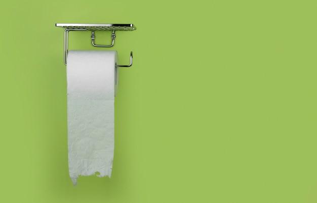 Rolka biały papier toaletowy na tle zieleni ściany kopii przestrzeń. niedobór papieru toaletowego.