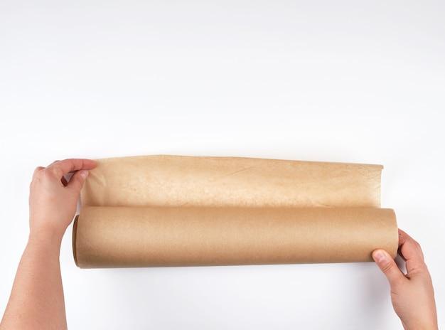 Rolka brown pergaminowy papier dla piec jedzenie w żeńskich rękach