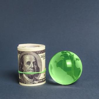 Rolka dolarów i zielona kula ziemska. międzynarodowe transfery pieniężne, inwestycje przyciągające