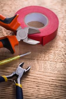 Rolka dwóch szczypiec taśmy izolacyjnej i tester na koncepcji budowy drewnianej deski