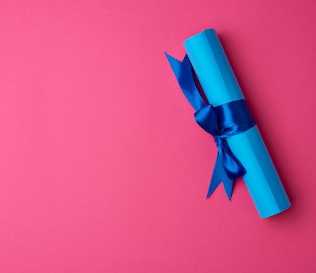 Rolka niebieskiego papieru przewiązana jedwabną niebieską wstążką