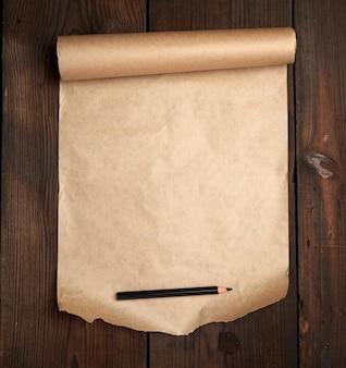 Rolka nieskręconego brązowego papieru na drewnianej powierzchni ze starych desek