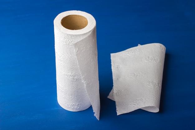 Rolka papierowy ręcznik na błękitnym, drewnianym tle.