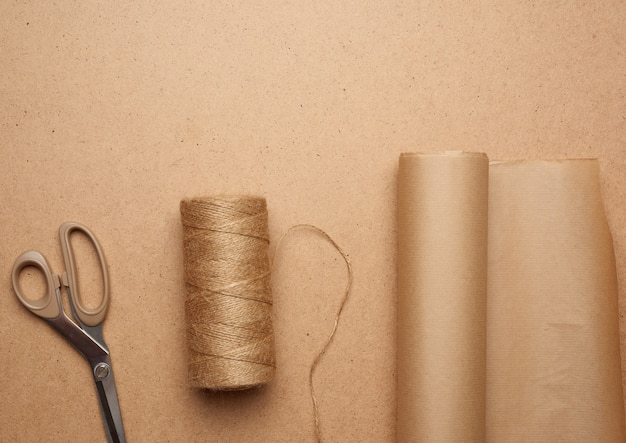Rolka papieru brązowego rzemiosła, motek nici i nożyczki