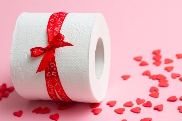 Rolka papieru toaletowego jako prezent na walentynki, obok czerwonych serduszek na różowo