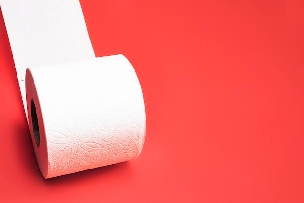 Rolka papieru toaletowego na czerwonym tle.