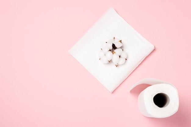Rolka ręczników papierowych i bawełnianych kwiatów na różowej powierzchni. concept to 100 produktów naturalnych, delikatnych i miękkich. leżał płasko, widok z góry