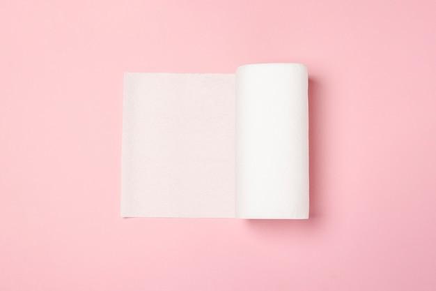 Rolka ręczników papierowych na różowej powierzchni. concept to 100 produktów naturalnych, delikatnych i miękkich. leżał płasko, widok z góry.