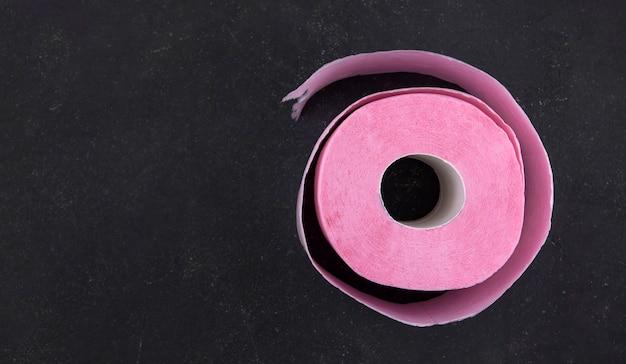 Rolka różowy papier toaletowy na ciemnoszarym tle kopii przestrzeni. niedobór papieru toaletowego.