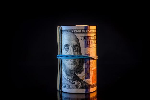 Rolka stu dolarowych banknotów na czarnym tle