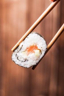 Rolka sushi z bliska między parą pałeczek