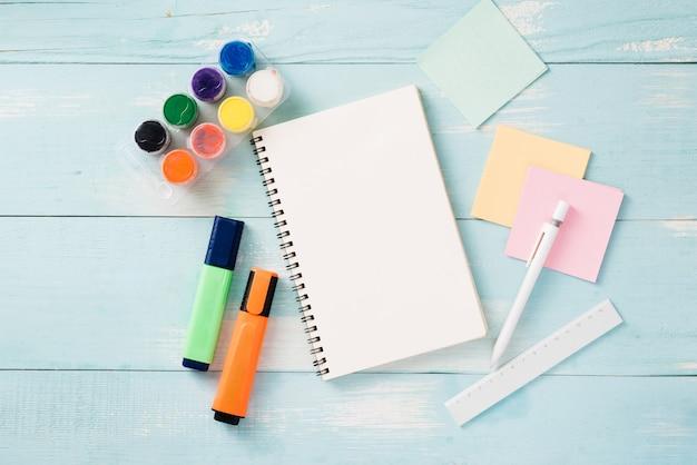 Rolka taśmy papierowej, spinacze do papieru i notatniki leżące na drewnianym stole, przybory szkolne, artykuły biurowe, powrót do szkoły