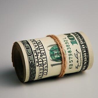 Rolka z bliska sto dolarów amerykańskich na szarej powierzchni. zbliżenie, wolne miejsce na podpisy i tekst.