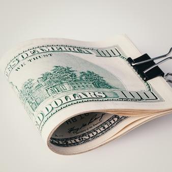 Rolka z bliska sto dolarów amerykańskich na szarej ścianie. zbliżenie, wolne miejsce na podpisy i tekst.
