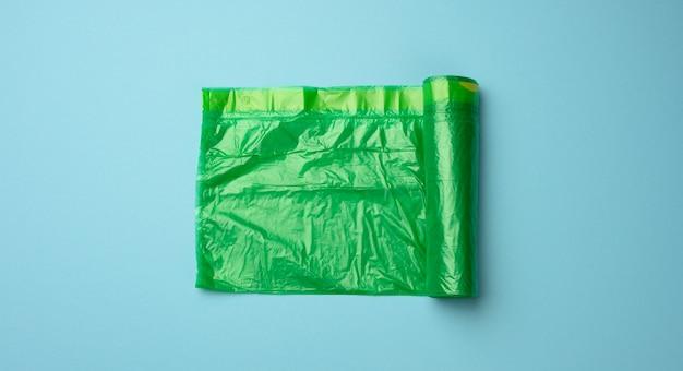 Rolka zielonych przezroczystych plastikowych toreb na kosz na śmieci na niebieskim tle, widok z góry