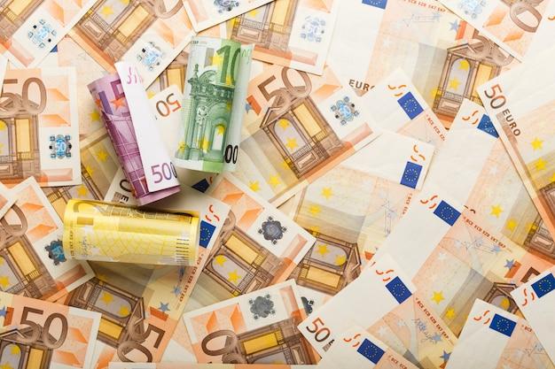 Rolki banknotów euro na rozrzucone pieniądze euro. biznes, finanse, oszczędności, koncepcja bankowości, kursy walut. rama, kopia przestrzeń, widok z góry.